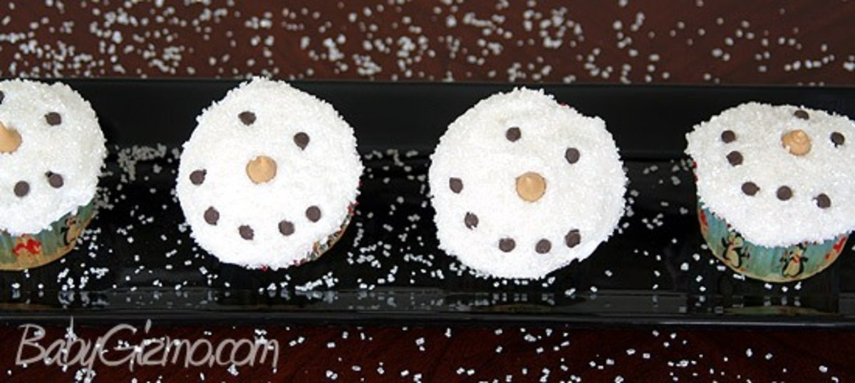 4 snowman cupcakes on a black plate